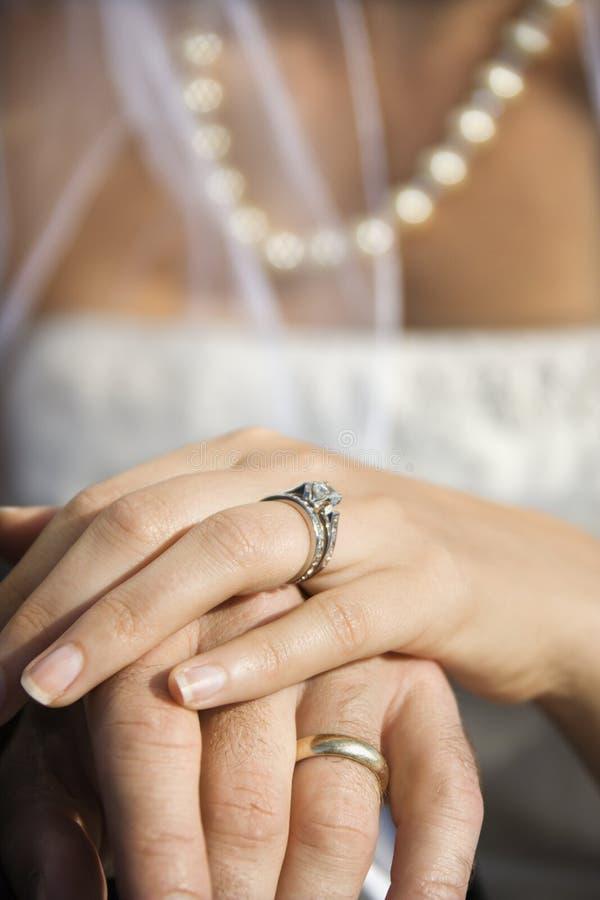 De hand van de bruid bovenop bruidegom stock fotografie