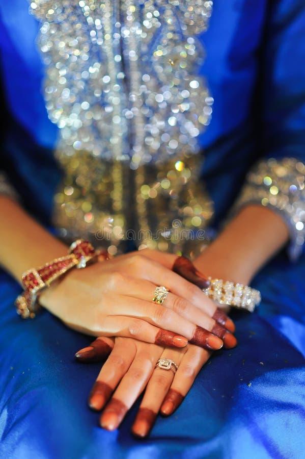 De hand van de bruid met diamantring, die een blauwe huwelijkskleding dragen royalty-vrije stock fotografie