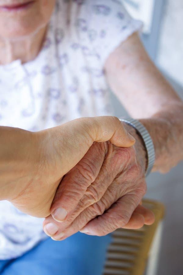 De hand van de holdingsoudsten van Caregiver royalty-vrije stock fotografie
