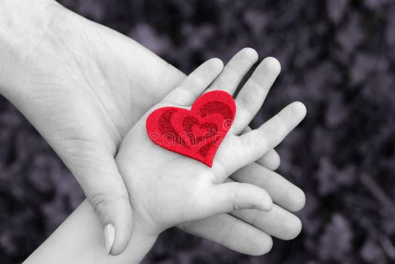 De hand van de moeder en van de baby met rood hart stock afbeelding