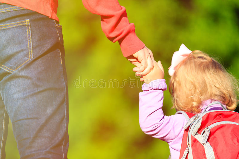 De hand van de moederholding van weinig dochter in openlucht stock foto's