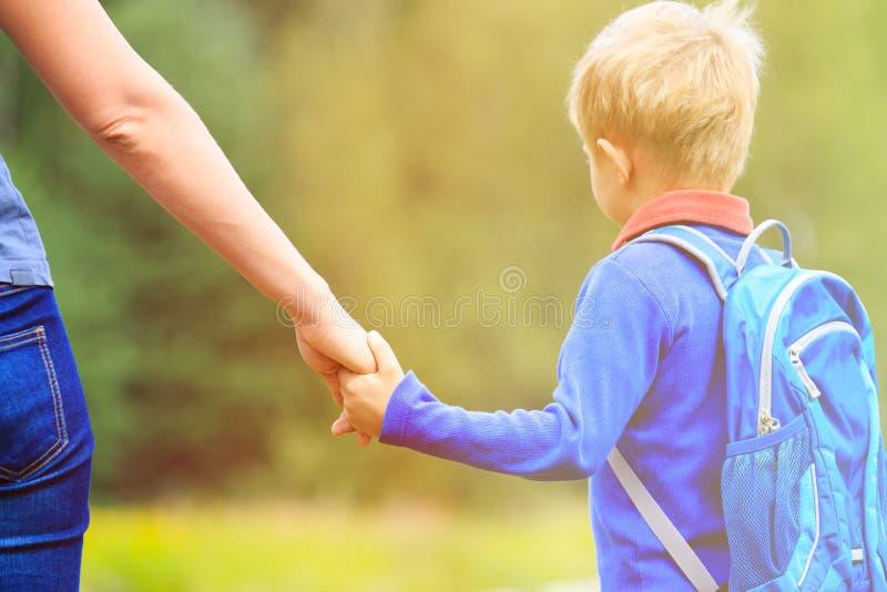De hand van de moederholding van weinig zoon met rugzak royalty-vrije stock foto's