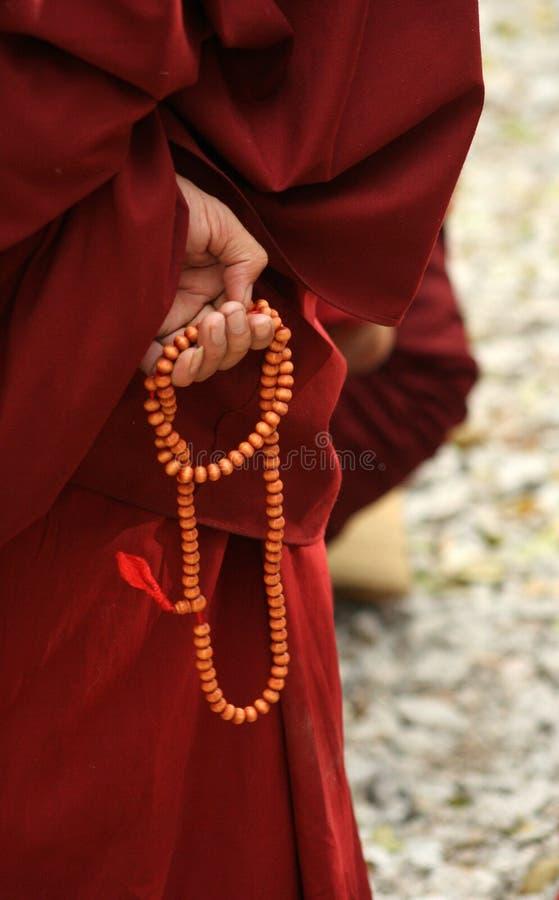 De hand van de monnik met parel stock foto