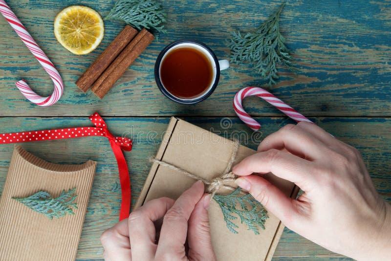 De hand van de vakjes van vrouwenpakken met Kerstmisgiften stelt op een houten lijst voor stock foto