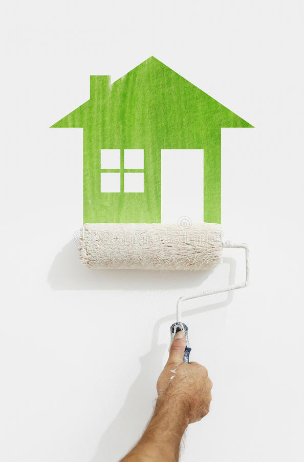 De hand van de verfrol met het groene huissymbool schilderen op muurisola stock afbeelding