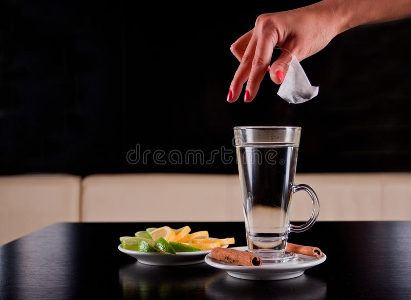 De hand van de vrouw het dalen theezakje in heet waterglas stock foto