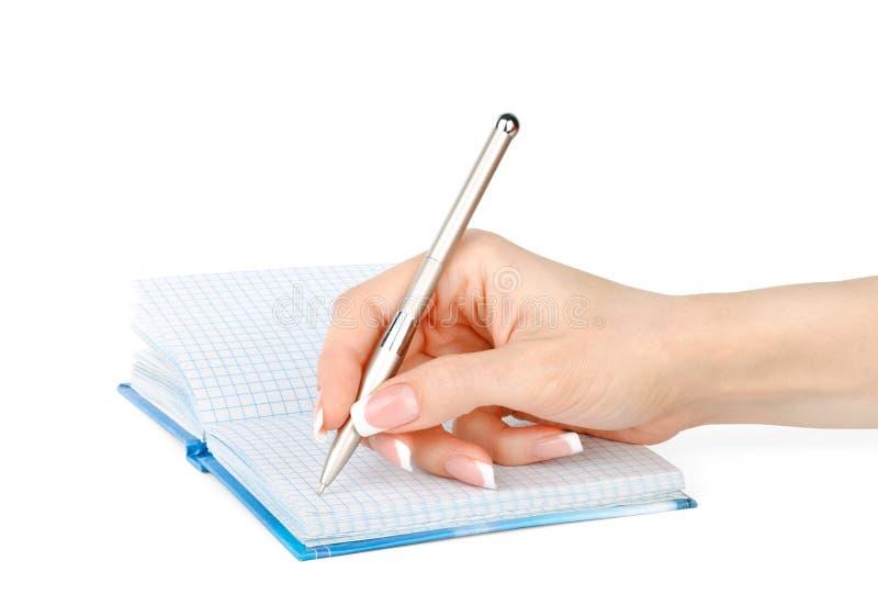 De hand van de vrouw met een pen schrijft in een geïsoleerd notitieboekje stock foto's