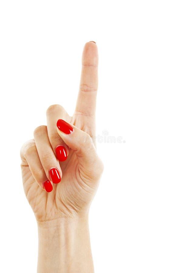 De hand van de vrouw met rode spijkers die met wijsvinger richten royalty-vrije stock afbeelding
