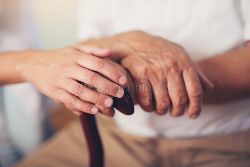 De hand van de vrouwenholding van de oude mens met wandelstok stock fotografie