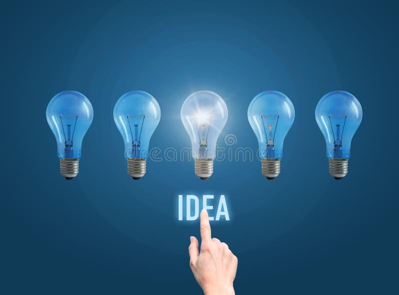 De hand van de zakenman klikt op de knoop het idee en stak de lamp aan stock afbeelding