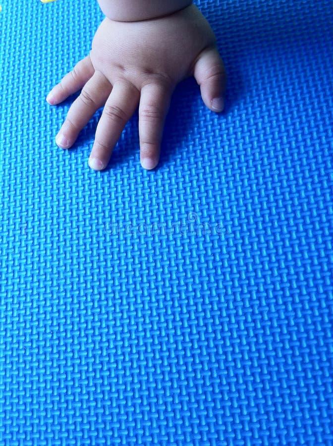 De Hand Van De Zuigeling Op De Mat Stock Afbeeldingen
