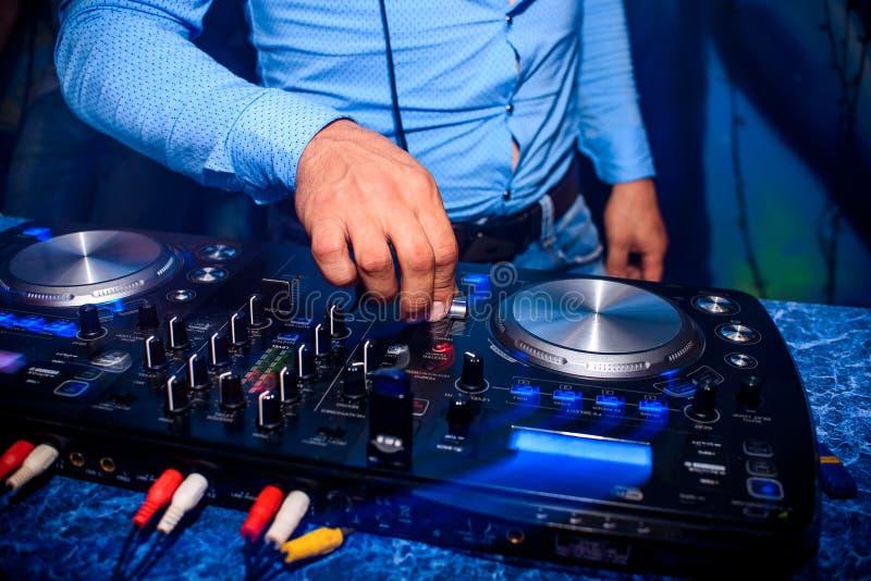 De hand van DJ controleert volume en mengelingsmuziek in professionele mixer in nachtclub bij partij royalty-vrije stock fotografie
