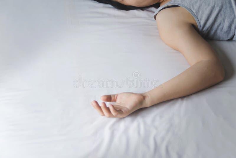De hand van drukt en het hopeloze vrouw leggen op bed in royalty-vrije stock afbeelding