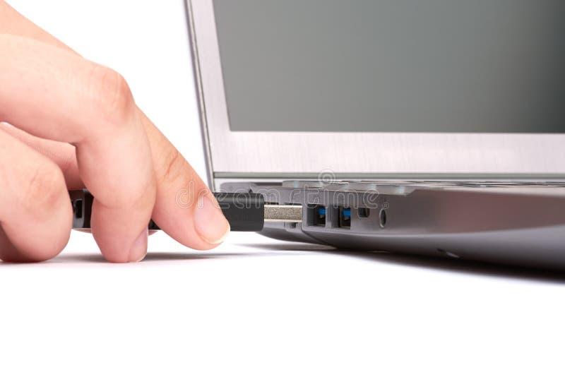 De hand van een jonge vrouw verbindt een USB-flashstation met een haven in laptop met een zwart toetsenbord Ge?soleerdj op witte  stock afbeeldingen