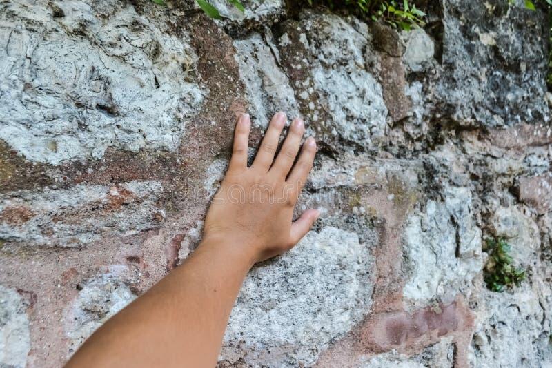 De hand van een jonge witte vrouw raakt de muur raak de antiquiteit stock foto