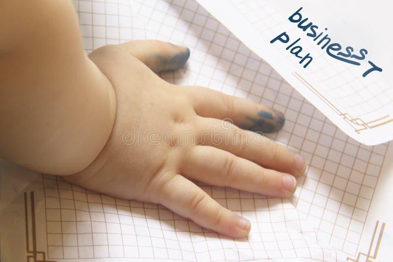 De hand van een klein kind is bevlekt in inkt liggend op een stuk van document concept een beginner in zaken Het Businessplan van stock foto