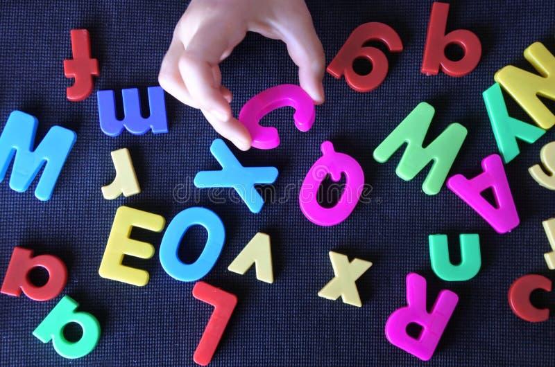 De hand van een klein kind leert het engelstalige alfabet stock afbeeldingen
