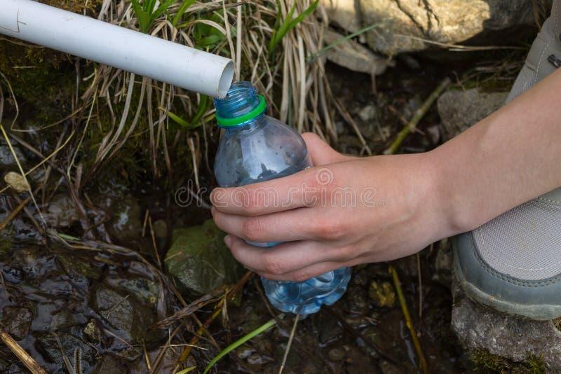 De hand van een meisje dat water in een plastic flessenclose-up verzamelt royalty-vrije stock afbeeldingen