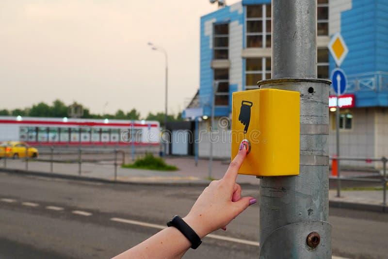 De hand van een meisje met een klok drukt de knoop van de voetgangersoversteekplaats De knoop wordt aangestoken in rode, elektron stock afbeeldingen