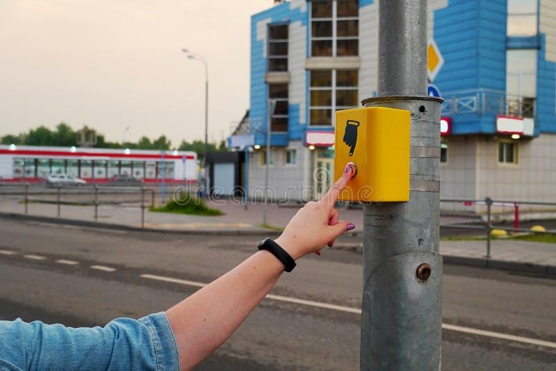 De hand van een meisje met een klok drukt de knoop van de voetgangersoversteekplaats De knoop wordt aangestoken in rood, elektron stock afbeelding