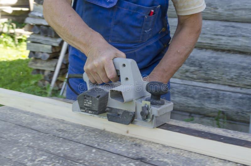 De hand van een mens die met planer en planer raad werken Timmerman die met elektrische planer aan houten plank werken openlucht royalty-vrije stock afbeeldingen