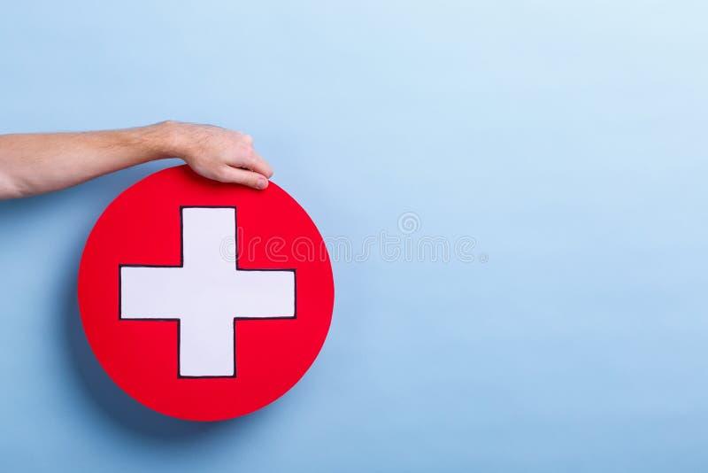De hand van een mens houdt een medisch teken, een kruis in een cirkel Blauwe achtergrond met een plaats voor een inschrijving stock foto