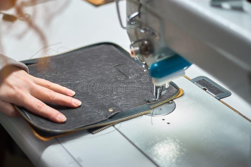 De hand van een ontwerper die die een fragment van een zak stikken stock fotografie