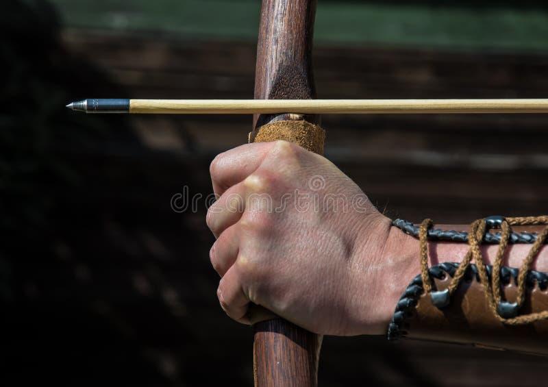 De hand van een schutter houdt boog en pijl en doelstellingen bij doel stock afbeelding