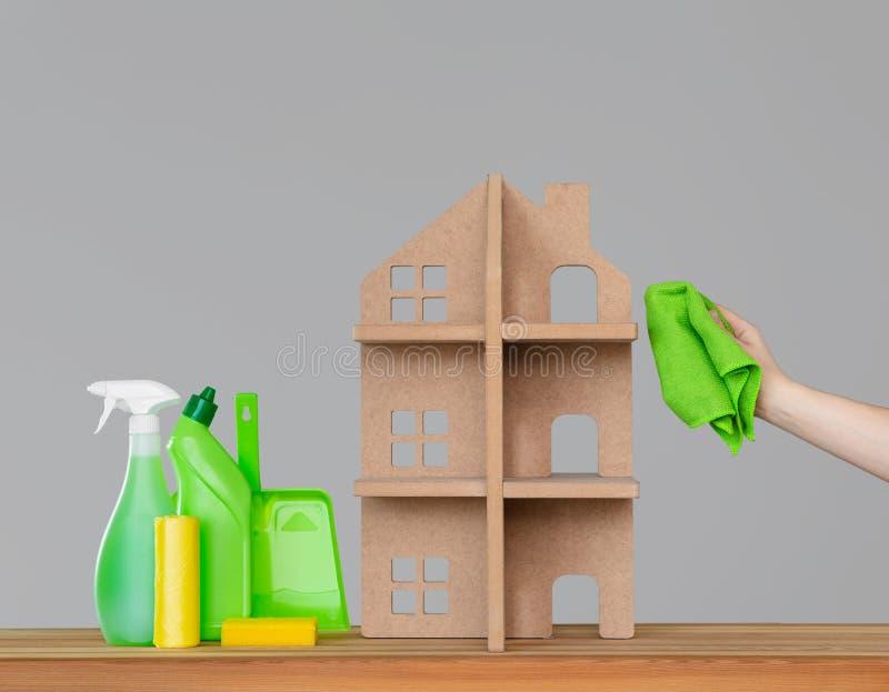 De hand van een vrouw wast het symbolische huis met een groene doek, naast het huis - een kleurrijke reeks hulpmiddelen om schoon royalty-vrije stock afbeelding
