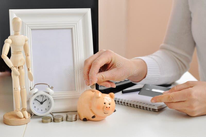 De hand van een vrouw zet geld in een spaarvarken, in de andere hand houdt een creditcard op de achtergrond van laptop, een klok, stock afbeelding
