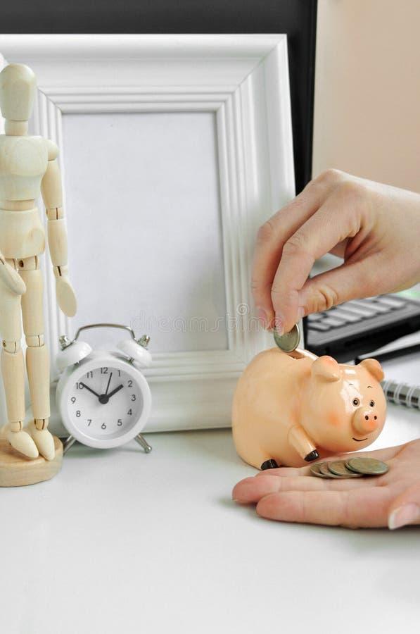 De hand van een vrouw zet geld in een spaarvarken op de achtergrond van laptop, een klok, een kader, een notitieboekje en een hou stock fotografie