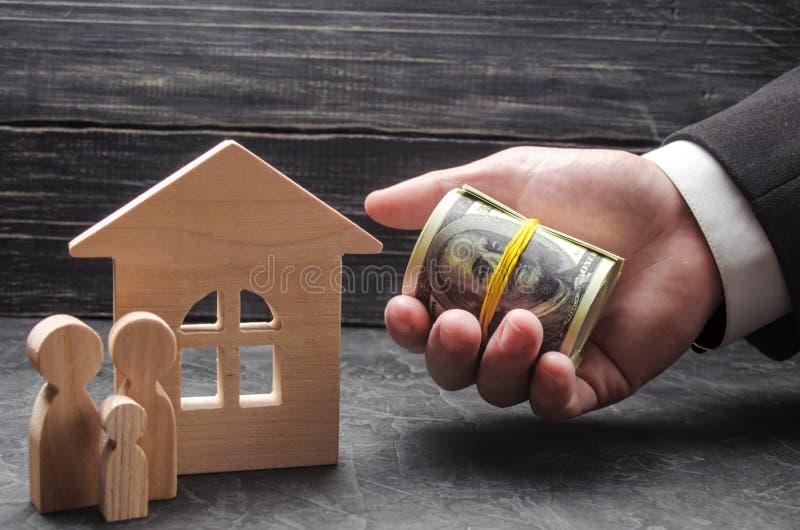 De hand van een zakenman breidt geld tot een blokhuis uit De familie bevindt zich dichtbij het huis Het concept het kopen royalty-vrije stock foto