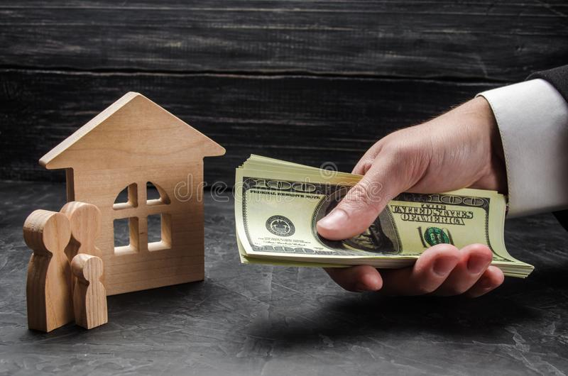 De hand van een zakenman breidt geld tot houten familiecijfers en een blokhuis uit Het concept het kopen en onroerende goederen v royalty-vrije stock foto's