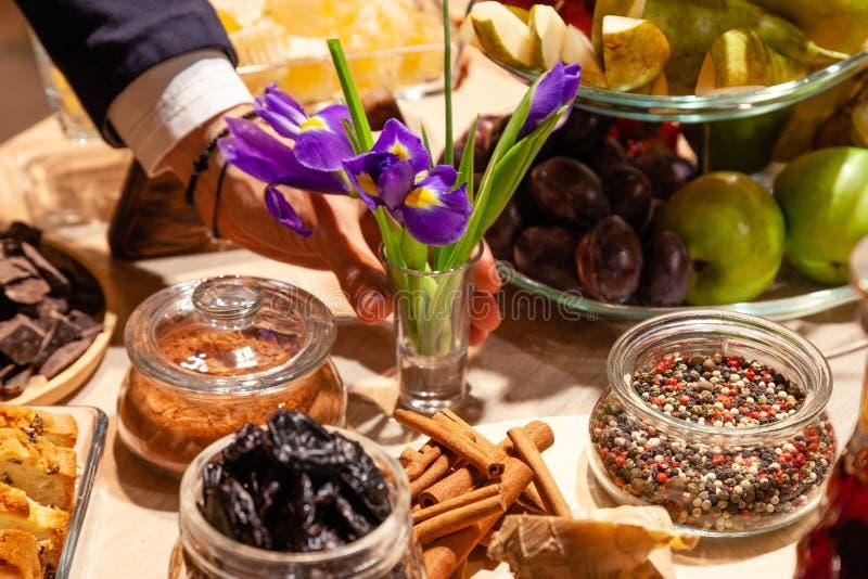 De hand van de elegante mens met leerarmband zet bloemen, purpere irissen in glasvaas tegen een buffetlijst met traktaties en sna stock afbeeldingen