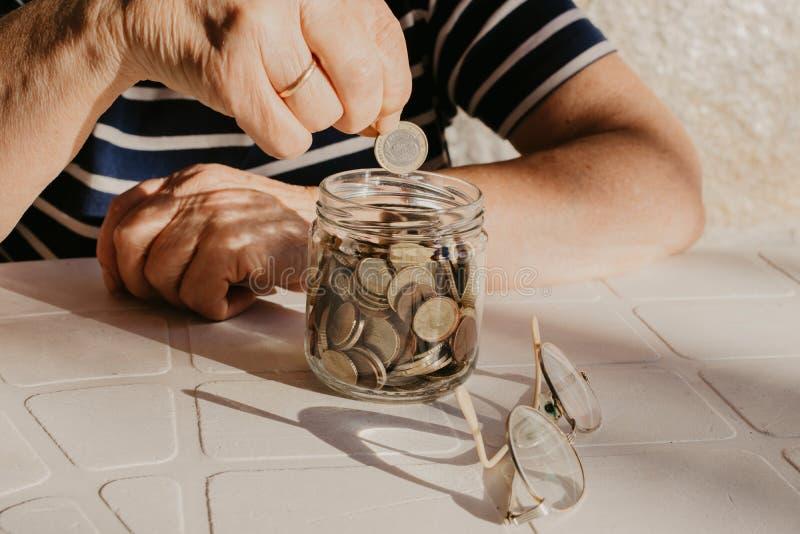 De hand van de gepensioneerde met besparingen stock foto