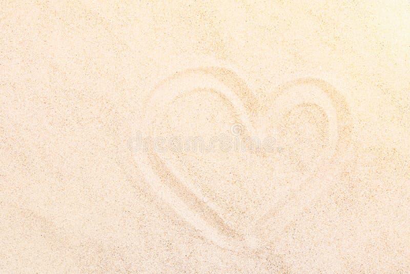 De Hand van de hartvorm op het Witte Fijne Strand van Zandar door de Oceaan wordt getrokken die De romantische Valentijnskaarten  stock foto