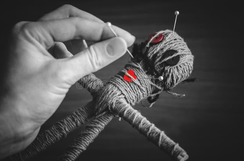 De hand van heks speldt een voodoopop tijdens oud ritueel close-up stock fotografie