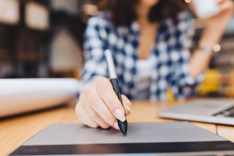 De hand van het close-upbeeld van vrouw het ontwerpen op lijst in het werkmateriaal van de bibliotheekrand Laptop, het creatieve  stock afbeeldingen