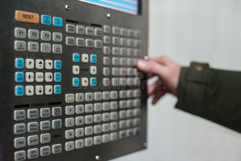 De hand van het exploitantgebruik draait de controle van de wijzerplaatschakelaar bij paneel van CNC draaibankmachine bij fabriek stock foto