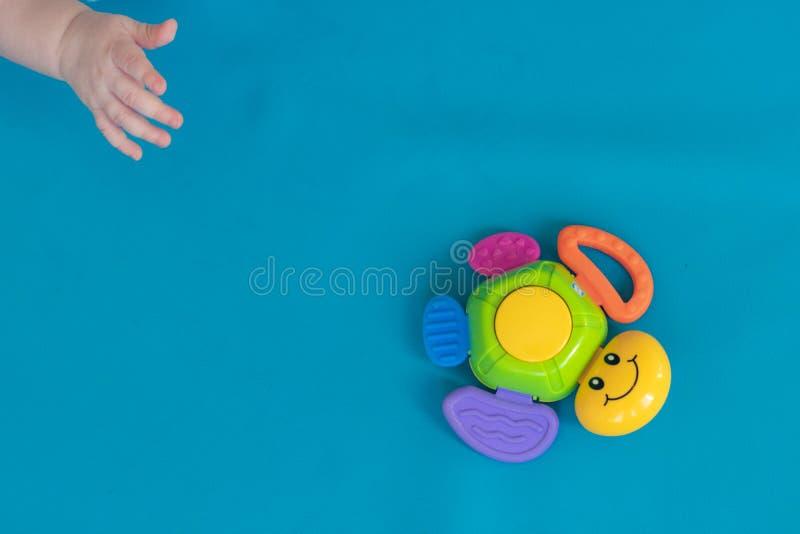 De hand van het kind bereikt voor een multicolored stuk speelgoed schildpad, welke het hangen tegen een blauwe achtergrond diagon royalty-vrije stock foto's