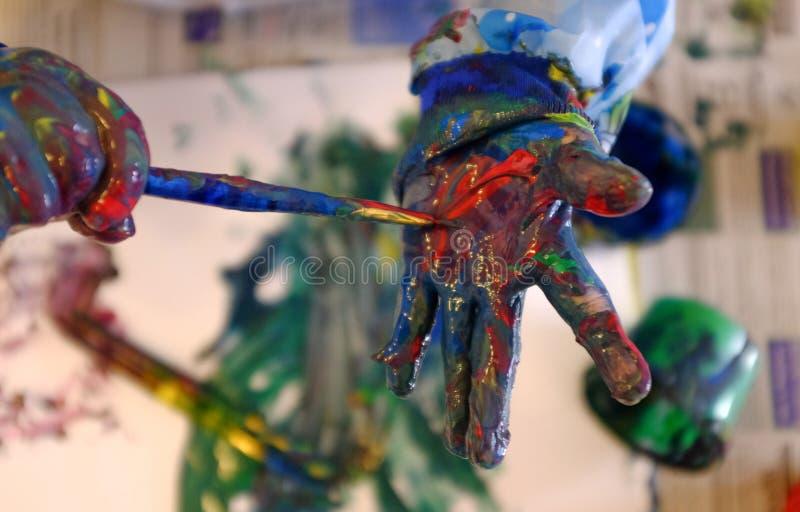 De hand van het kind die met verf wordt geschilderd royalty-vrije stock afbeeldingen