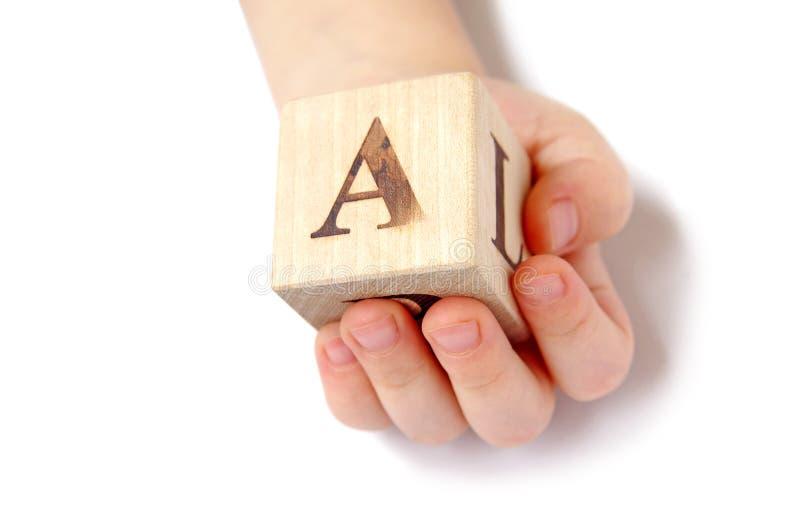 De hand van het kind en stuk speelgoed kubus stock foto's