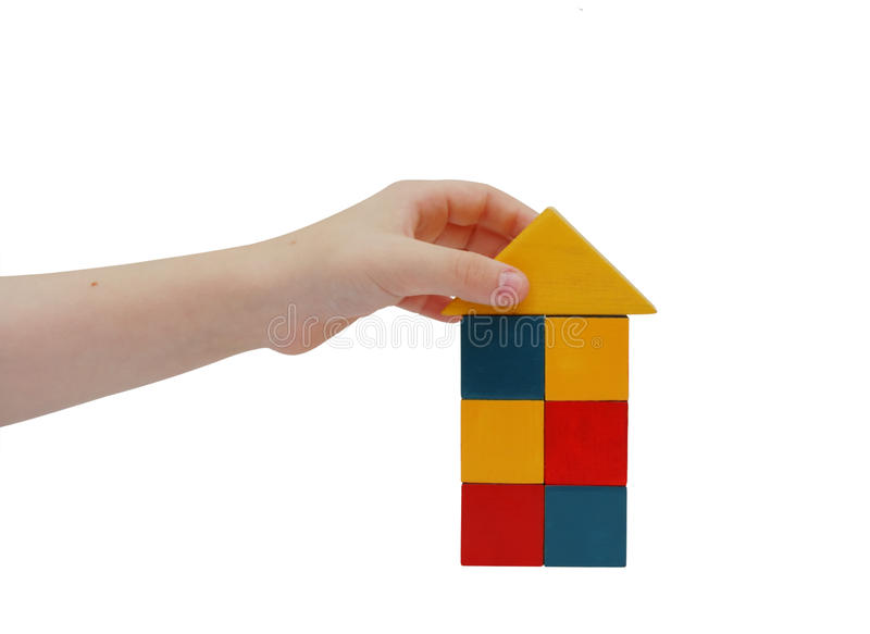 De hand van het kind maakt een gebouw met gekleurde blokken stock afbeelding
