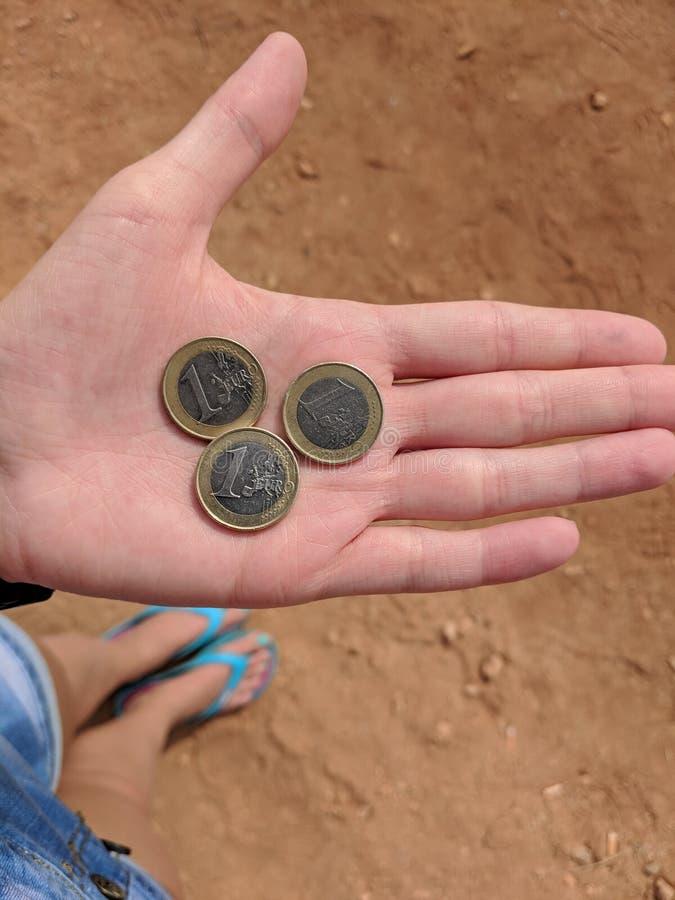 De hand van het meisje met drie euro in Cyprus stock afbeeldingen