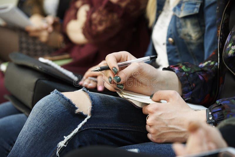 De hand van het meisje met een pen en een blocnote ligt op haar knieënclose-up royalty-vrije stock foto's