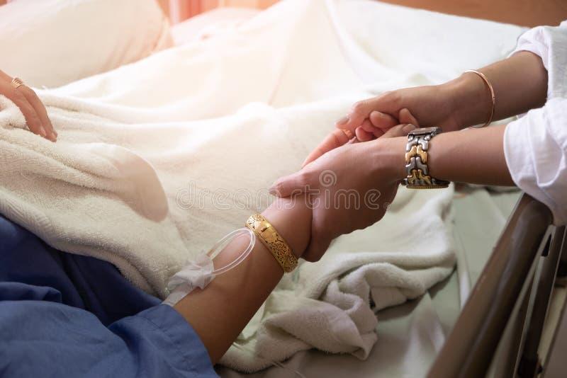 De hand van het meisje van de vrouwenholding die koortspatiënten in het ziekenhuis royalty-vrije stock fotografie