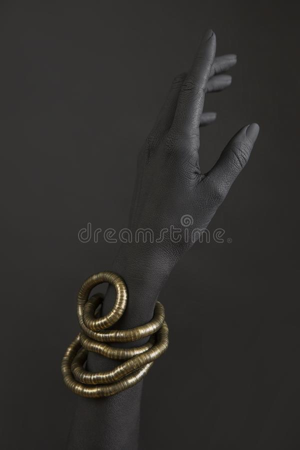 De hand van het zwarte met gouden juwelen Oosterse Armbanden op een zwarte geschilderde hand stock fotografie