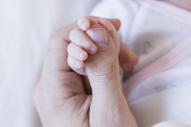 De hand van de de holdingsvader van het babykind, sluit omhoog mening Liefde en Familieconcept stock foto's