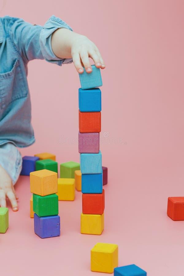 De hand van kinderen bouwt een toren van houten gekleurde kubussen stock foto