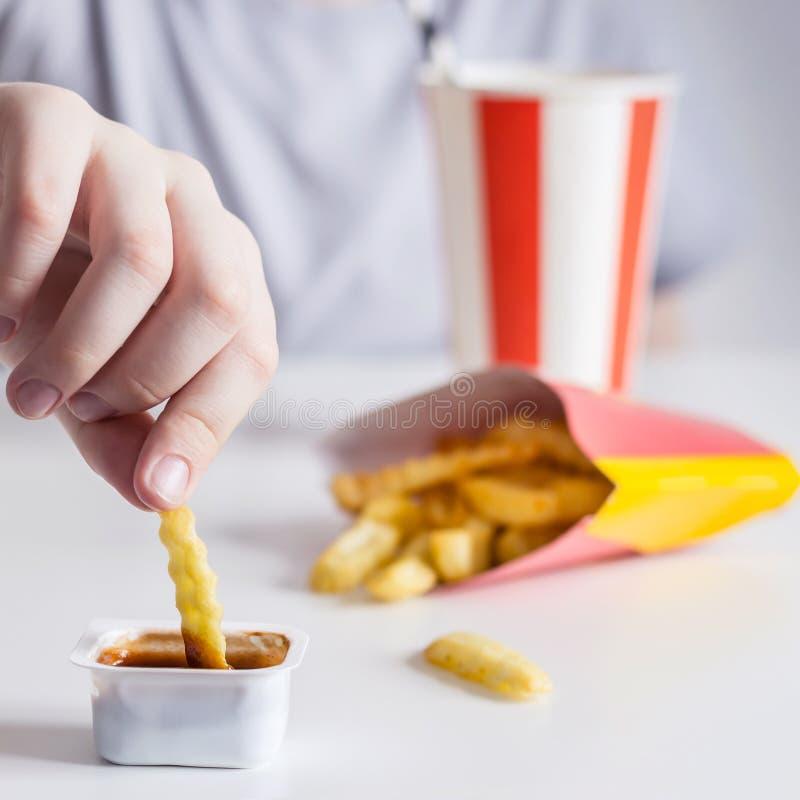 De hand van kinderen dompelt frieten in sausclose-up onder, selectieve nadruk stock foto